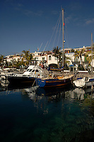 Boats moored alongside palms trees and colourful houses and apartments in Mogan, designed on Venice style. Gran, Canaria,Canary Islands, Spain.