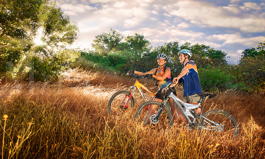 Young couple mountain biking through a golden field.