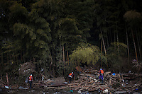 Rescue workers search for bodies amongst debris on the edge of a forest. Thousands of people died in this small town which ran out of body bags. On 11 March 2011 a magnitude 9 earthquake struck 130 km off the coast of Northern Japan causing a massive Tsunami that swept across the coast of Northern Honshu. The earthquake and tsunami caused extensive damage and loss of life.