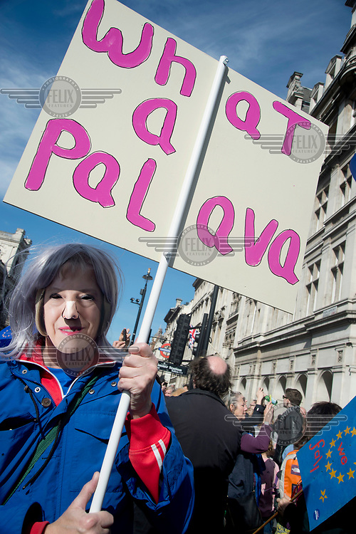 A woman in a Theresa May face mask carries a placard that reads: 'What a palava' at a 'Unite for Europe March on Parliament'.