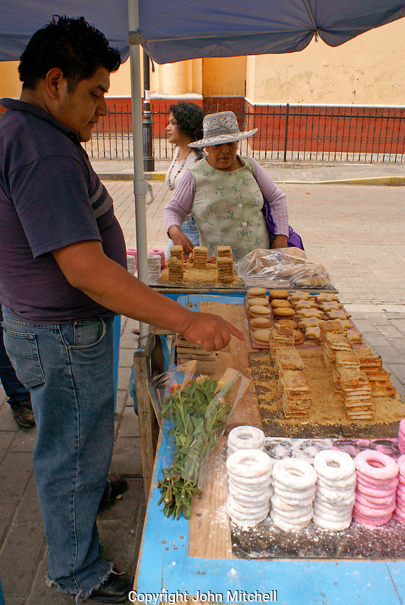 Woman buying sweets from a street vendor in Cholula, Puebla, Mexico. Cholula is a UNESCO World Heritage Site.