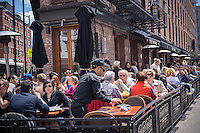 Busy al fresco dining at sidewalk cafes in the Meatpacking District in New York on Sunday, May 26, 2013. (© Richard B. Levine)