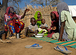 Fatna eats with her children in a camp for internally displaced persons outside Kubum, in South Darfur, where ACT-Caritas is providing water, sanitation and other emergency services.