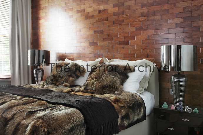 Wooden brick cladding is an unusual feature of this bedroom, while fur covers give it a touch of Finnish style