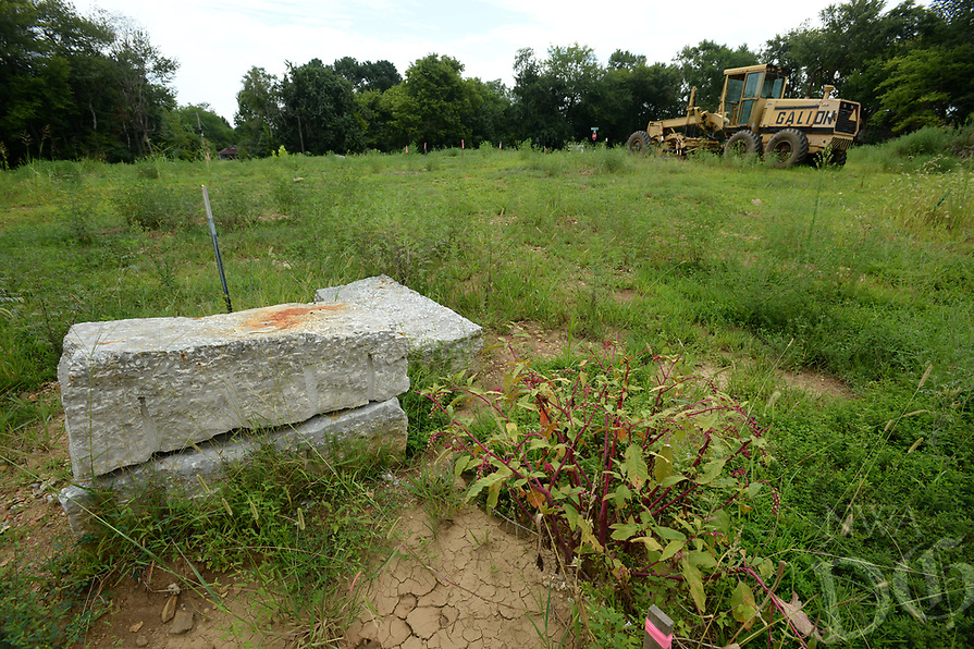 NWA Democrat-Gazette/ANDY SHUPE<br /> Poke grows in an empty lot Tuesday, Aug. 13, 2019, near a grader at the Homes at Willow Bend project, a development by Partners for Better Housing.The project involves building about 80 homes for families of mixed incomes with affordable financing available. It broke ground in 2017.