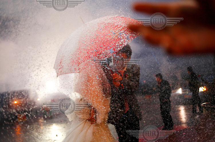The bride and groom shelter beneath an umbrella from a shower of celebratory foam being sprayed all around them.