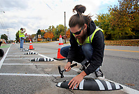 NWA Democrat-Gazette/DAVID GOTTSCHALK  Blake Kingfisher, a volunteer, taps caps Friday, November 2, 2018, over bolts on a Zebra, a bike lane delineator and product from Spain, on the protected bike lanes on Holcomb street in Springdale. Bike NWA is the pilot project owner working with Lane Shift the consultant that planned, designed and installed the bike lanes.
