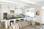 Shaker-style white cabinetry and dark stone countertops in an open and airy kitchen. This image is available through an alternate architectural stock image agency, Collinstock located here: http://www.collinstock.com