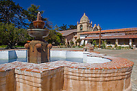 Monterey County, CA<br /> Courtyard fountain frames the cloister walk and tower of the Carmel Mission Basilica (1797) - Mission San Carlos Borromeo del Rio Carmelo
