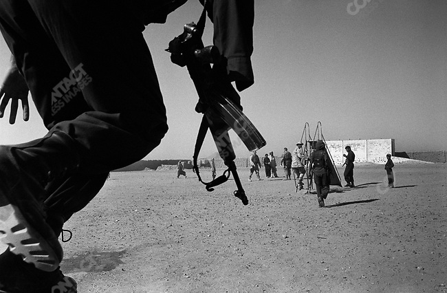 Afghan Special Forces soldier leaps over a school wall in refugee camp near Kandahar. September 29th 2005.