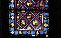 Detail of stained glass window with Fleur de lys and Castillan castles which symbolize Saint Louis and his mother, Blanche de Castille, La Sainte-Chapelle (The Holy Chapel), 1248, Paris, France. La Sainte-Chapelle was commissioned by King Louis IX of France to house his collection of Passion Relics, including the Crown of Thorns. The Sainte-Chapelle is considered among the highest achievements of the Rayonnant period of Gothic architecture. Picture by Manuel Cohen