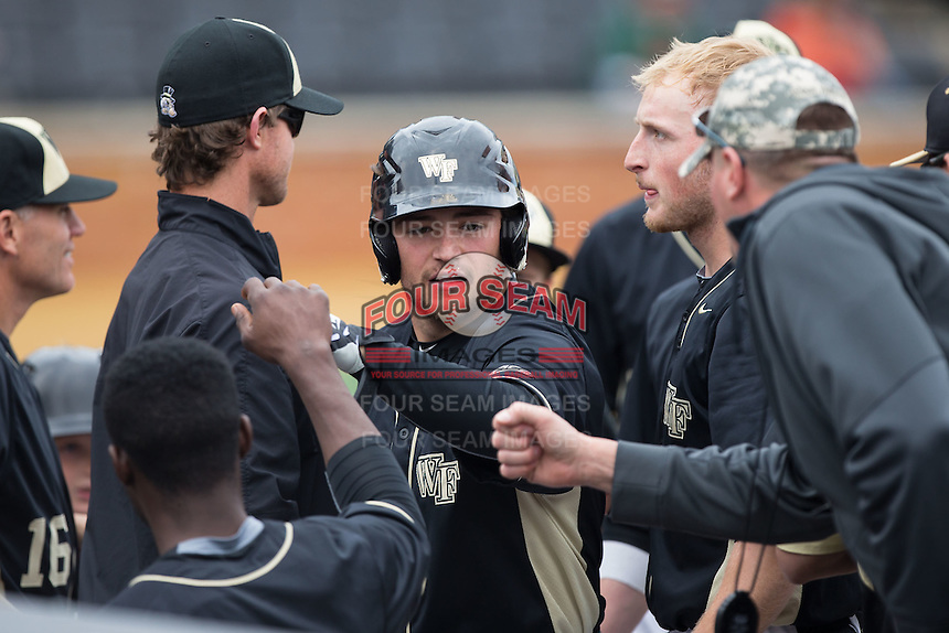 Nate Mondou (10) of the Wake Forest Demon Deacons high fives teammates after scoring a run against the Miami Hurricanes at Wake Forest Baseball Park on March 22, 2015 in Winston-Salem, North Carolina.  The Demon Deacons defeated the Hurricanes 10-4.  (Brian Westerholt/Four Seam Images)