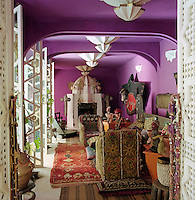 The purple living room is furnished with an eclectic collection of furniture and artwork
