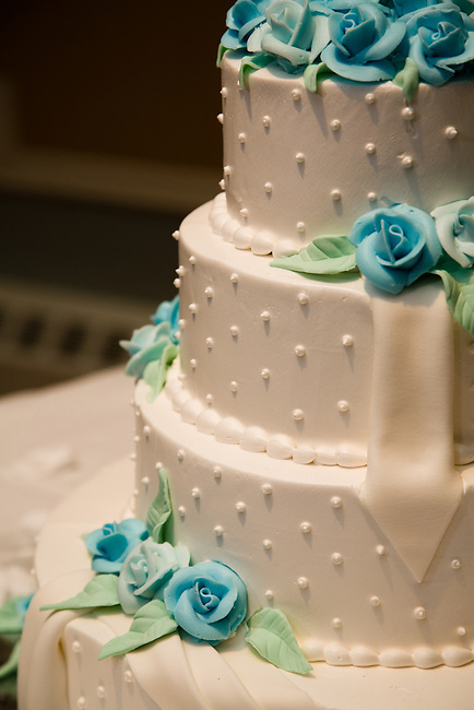 Close-up of a wedding cake decorated with blue confectionery roses.