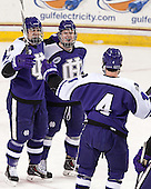 Jake Youso (HC - 11) and Joe McNamara (HC - 4) celebrate with goal scorer Mike Barrett (HC - 29). - The visiting College of the Holy Cross Crusaders defeated the Boston College Eagles 5-4 on Friday, November 29, 2013, at Kelley Rink in Conte Forum in Chestnut Hill, Massachusetts.