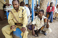 Somaliland. Sahil province. Berbera. Two soldiers, both black muslim men, with a kalaschnikov enjoy  tea with milk in a café. One is seated, the other kneeled down. Somaliland is an unrecognized de facto sovereign state located in the Horn of Africa.  © 2006 Didier Ruef