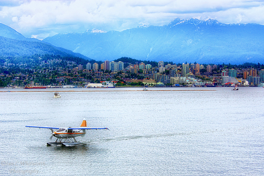 A seaplane taxiing to the water airport with North Vancouver in the background