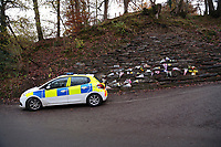 Pictured: Police by flowers and tributes left at the entrance to the lane leading to the house that was burned in a fire in Llangammarch Wells, Wales, UK. Tuesday 07 November 2017<br /> Re: Dyfed Powys Police press conference at Llandrindod Wells over a house fire that killed a father and his children in Llangammarch Wells, mid Wales, UK. <br /> David Cuthbertson, 68, and the children aged between four and 11 are missing, presumed dead, following the blaze.<br /> Three other children aged 10, 12 and 13 escaped and were taken to hospital.<br /> Dyfed-Powys Police said they have been released and are being cared for by family.
