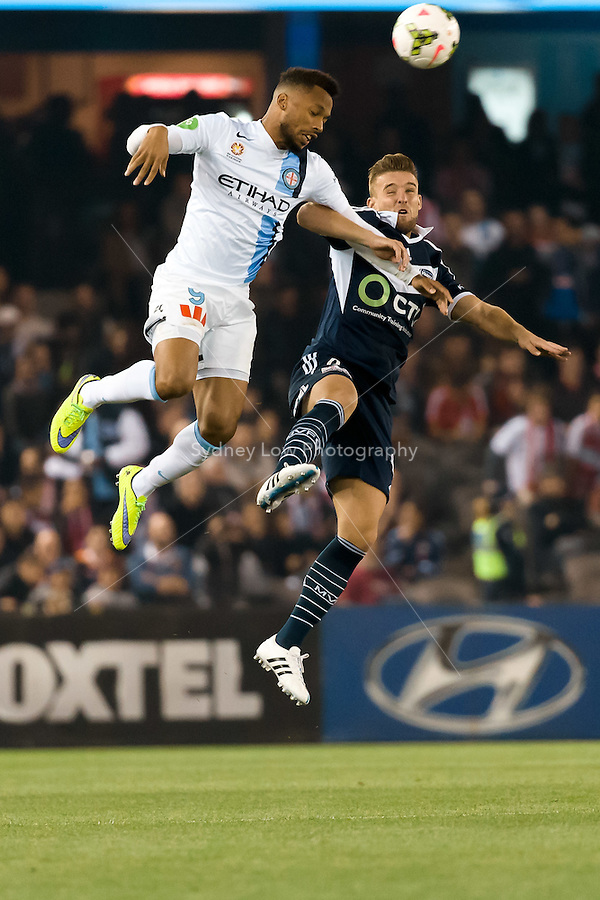 Harry Novillo of City and Nicholas Ansell of the Victory jump for the ball in the semi final match between Melbourne Victory and Melbourne City in the Australian Hyundai A-League 2015 season at Etihad Stadium, Melbourne, Australia.<br />