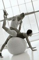 Personal training session: man assists woman with her workout using a therapy ball.
