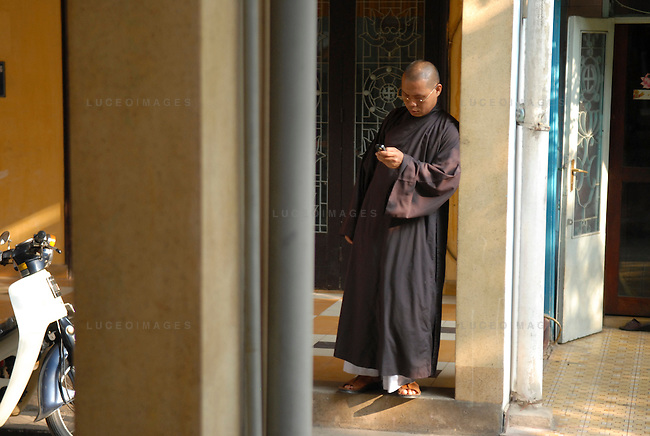A Buddhist monk text messages outside of his pagoda in Ho Chi Minh City, Vietnam.