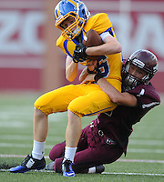 STAFF PHOTO ANDY SHUPE -  Hot Springs Lakeside  receiver Blake Spilker is tackled by Lincoln linebacker Charles Rowe during the first half of play Monday, Sept. 1, 2014, at Razorback Stadium in Fayetteville.