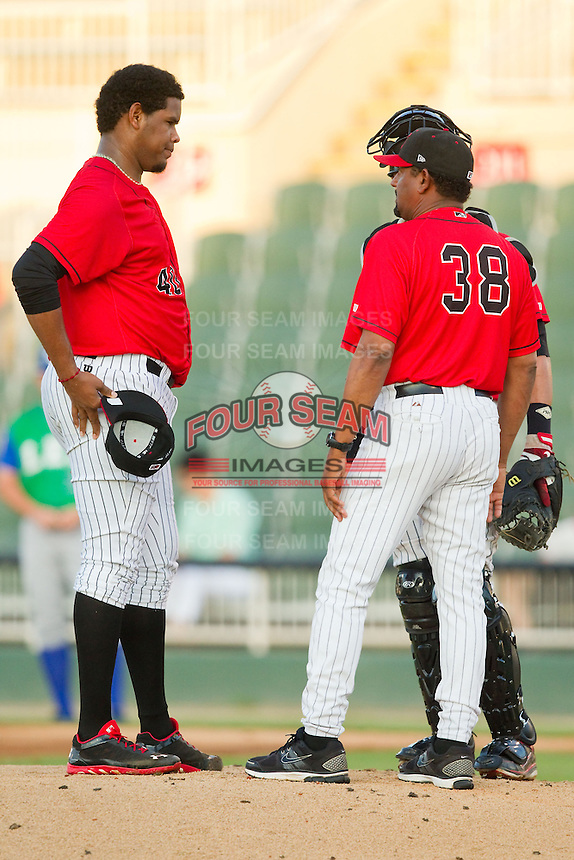 Kannapolis Intimidators pitching coach Jose Bautista (38) has a chat on the mound with starting pitcher Jefferson Olacio (40) during the South Atlantic League game against the Lexington Legends at CMC-Northeast Stadium on July 29, 2013 in Kannapolis, North Carolina.  The Intimidators defeated the Legends 10-5.  (Brian Westerholt/Four Seam Images)