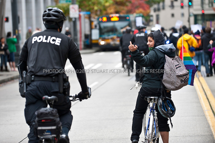 10/22/2011--Seattle, WA, USA..A protesters flips the bird at a police man during anti-police and Occupy Seattle protests...Occupy Seattle, a spin off of the Occupy Wall Street protests in New York City, joined an anti-police brutality march in downtown Seattle with over 500 protesters, including a few black masked anarchists and other radicals. ..The Occupy Seattle protest has attempted to set up a base in Seattle's Westlake Park in the heart of the city but the Seattle Police Department has arrested anyone attempting to set up tents...©2011 Stuart Isett. All rights reserved.