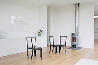 Minimalist white room with wooden flooring, steel wood burning stove and designer chairs