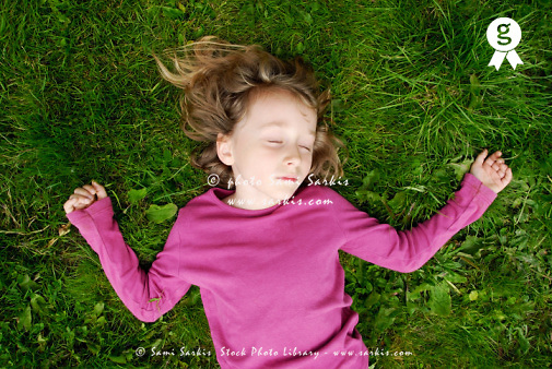 Girl (6-7) lying down in grass with eyes closed, overhead view (Licence this image exclusively with Getty: http://www.gettyimages.com/detail/sb10065474z-001 )