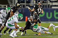 1 September 2011:  FIU running back Darriet Perry (28) is tripped up by North Texas linebacker Jeremy Phillips (45) in the first half as the FIU Golden Panthers defeated the University of North Texas, 41-16, at FIU Stadium in Miami, Florida.