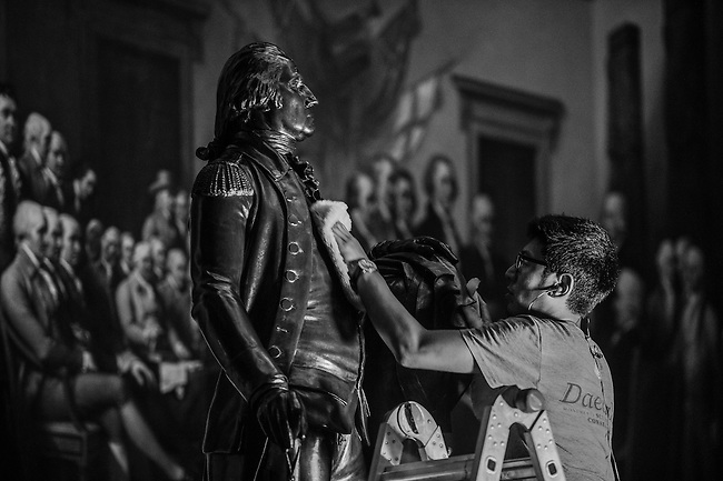 "UNITED STATES - JUNE 16: Gompo Yarmolinsky, of Daedalus Conservators, rubs the chest of the George Washington statue in the Capitol Rotunda after vacuuming the statue on Tuesday evening, June 16, 2015. John Trumbull's ""Declaration of Independence"" painting serves as a backdrop. (Photo By Bill Clark/CQ Roll Call)"