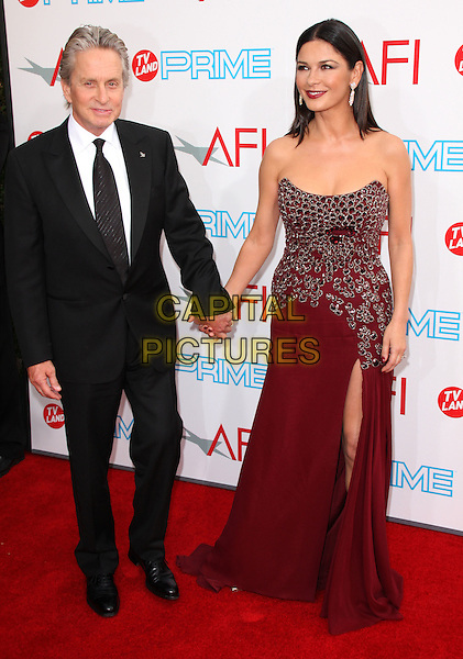 MICHAEL DOUGLAS & CATHERINE ZETA-JONES.37th Annual AFI Lifetime Achievement Awards held at Sony Pictures Studios, Culver City, California, USA..June 11th, 2009.full length red maroon burgundy jewel encrusted embellished dress strapless holding hands black suit slit split married husband wife .CAP/ADM/KB.©Kevan Brooks/AdMedia/Capital Pictures.