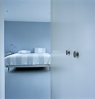 The entrance to this spacious contemporary bedroom is heralded by a built-in cupboard
