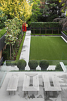 View of the garden from one of the upper floors, its modern design comprising of an immaculately kept lawn, paved paths and rigidly aligned trees and hedges. A glass walled patio area has also been created on top of the extension
