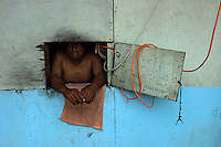 A resident looks out his makeshift window from inside a typical clapboard home in Ebeye, Marshall Islands on June 16, 2012. Most of the homes on Ebeye suffer from shoddy materials and construction.