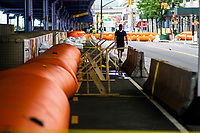 "NEW YORK, NY - AUGUST 4: A man walks next to water barriers used to prevent flooding at the South Street Seaport as city gets ready for tropical storm Isaias on August 4, 2020 in New York City. The Tri-State area ""New York, New Jersey and Connecticut"" is preparing for torrential rain, strong winds from Tropical storm Isaias. (Photo by Eduardo MunozAlvarez/VIEWpress)"