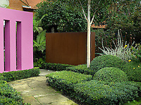 The old flagstone pathway bordered by geometric shapes of Buxus leads to the back garden