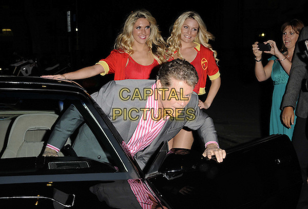 models & David Hasselhoff .The Clintons Celebrity Fastcard launch party, No. 5 Cavendish Square nightclub, Cavendish Square, London, England..October 18th, 2011.half length grey gray suit pink striped stripes shirt car bending leaning funny.CAP/CAN.©Can Nguyen/Capital Pictures.