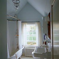 A salvaged brass shower mounted at one end of the claw-foot bath works well in this intimate bathroom