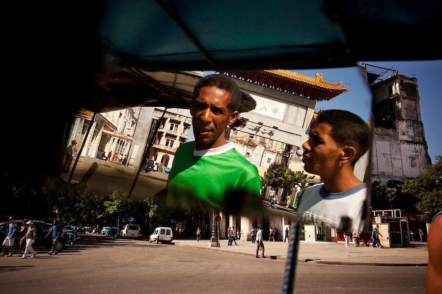 Bicycle taxi drivers wait for customers at the Chinatown archway, the entrance into Havana's Barrio Chino, on Saturday, April 26, 2008. Before the Cuban revolution, Barrio Chino was the largest Chinatown.in all of Latin America. Today, the neighborhood is a mere shadow of.its former self. Less than 300 Chinese-born immigrants live.throughout Cuba.