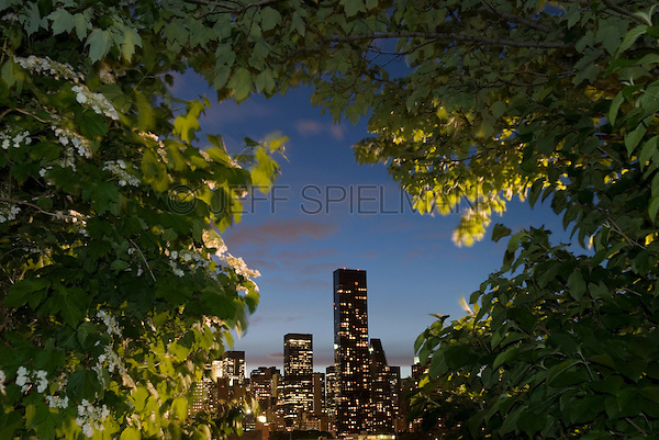 Available from Jeff as a Fine Art Print<br /> <br /> Available for commercial and editorial licensing exclusively from www.corbis.com. Please search for image # 42-22813748<br /> <br /> Midtown Manhattan Skyline viewed thru Trees in Queens, New York City, New York State, USA