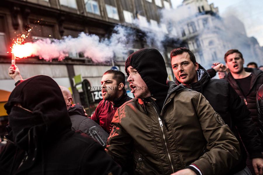 """BRUXELLES,Belgique: des hooligans sont arrivés place de la Bourse avec des flumigènes en criant """"Belgian hooligans, on est chez nous """", le 27 mars 2016. Peu après 14h, environ 400 hooligans sont arrivés à la Bourse et on semé le trouble au mémorial aux victimes des attentats de Bruxelles. Après 45min, la police est entrée en action pour encercler les individus et les repousser jusqu'à la gare du Nord."""