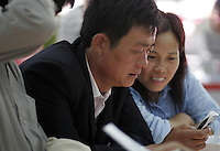 A Chinese couple looks at mobile phones on sale at an electronics store.