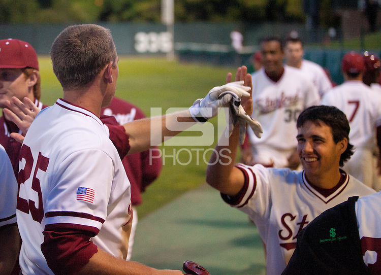 STANFORD, CA - April 12, 2011: Stephen Piscotty and Kenny Diekroeger of Stanford baseball high five after Piscotty scored during Stanford's game against Pacific at Sunken Diamond. Stanford won 3-1.