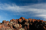Blue sky with wispy clouds behind a jagged lava rock formation.