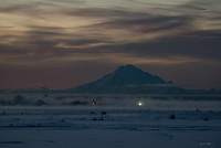 The sunset gives way to the Blue Hour around Alaska's Mount Redoubt as an ice fog rolls in over the Kenai River, obscuring houses along Kalifornsky Beach Road.
