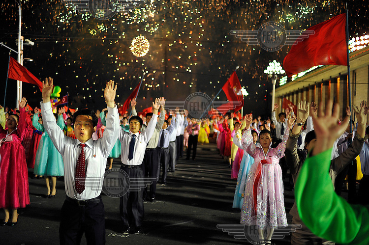 Fireworks explode behind a massed crowd of dancers, in Kim Il-sung Square, during celebrations marking the 100th birthday of Kim Il-sung.