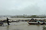 The Marowijne River, Suriname.  A maroon man tries to dislodge his boat from rocks in a rapid.