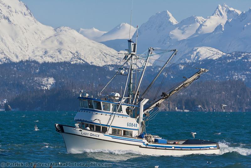 Commercial fishing purse seine boat passes through Kachemak Bay, Kenai Mountains, Kenai Peninsula, Alaska.